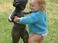 Little baby dancing with statues